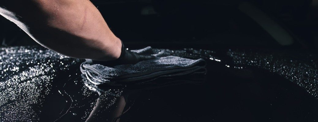 Image of a person's hand washing and waxing a black vehicle