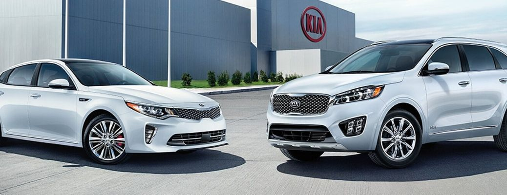 Exterior view of two silver Kia models parked outside of a Kia factory