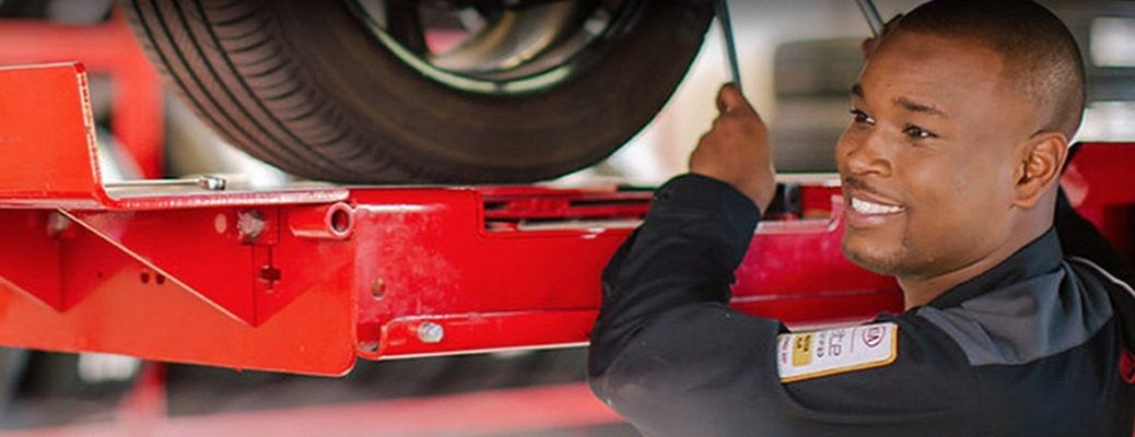 Image of a Kia service technician working underneath a vehicle