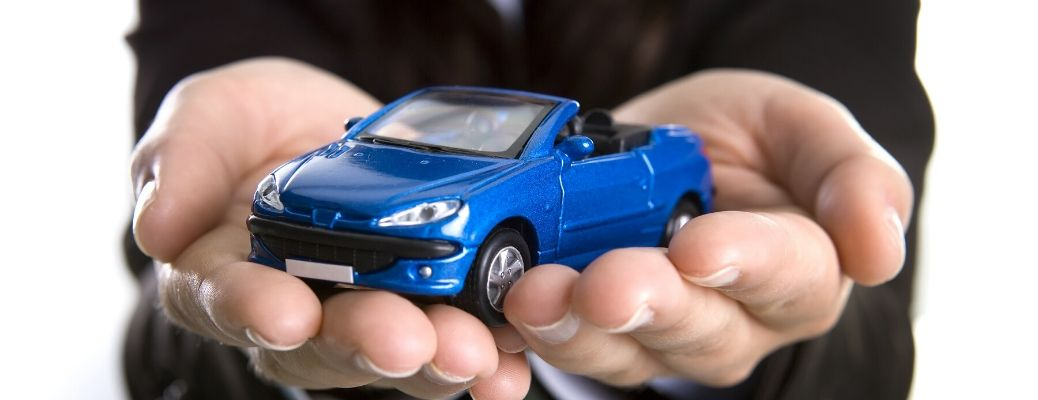 Image of hands holding a small blue toy car