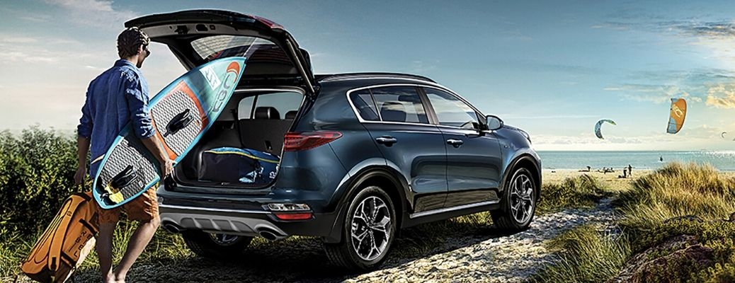 Exterior view of the rear of a blue 2020 Kia Sportage with its hatch open as a person loads their wake board in the back