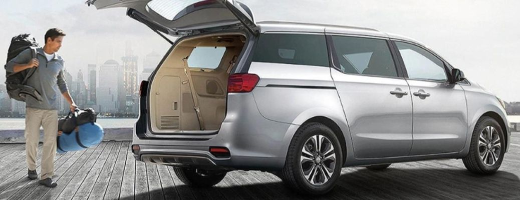 Exterior view of a silver 2021 Kia Sedona with the rear hatch open