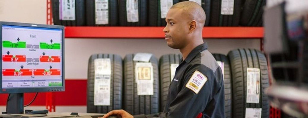 Image of a Kia tire center technician working on the computer in the tire center