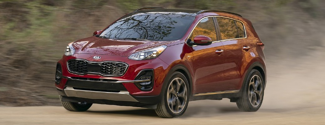 2021 Kia Sportage in a red color driving on a dirt road