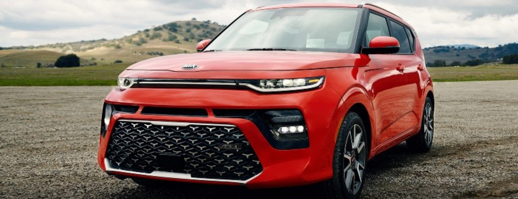 A red-colored 2021 Kia Soul driving on the road