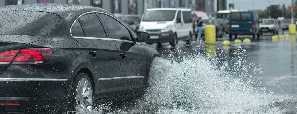 A car driving through a huge puddle on a road while it is raining