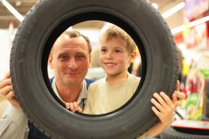 man and boy looking through tire_o