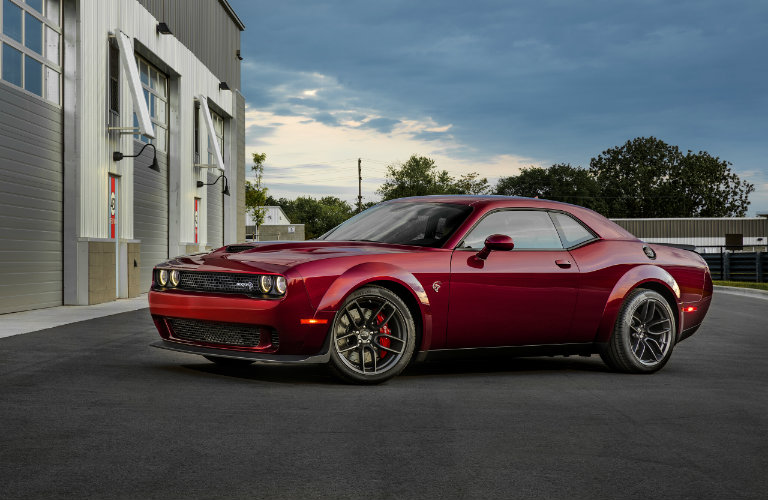Red 2018 Dodge Challenger SRT Hellcat Widebody parked near a garage, seen from the side