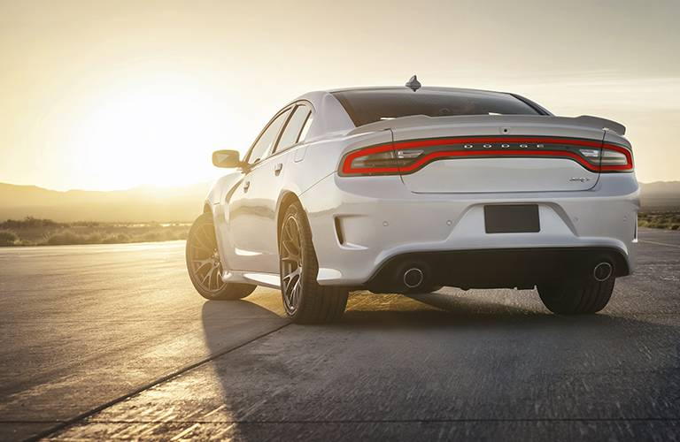 2016 Dodge Charger SRT sedan as seen from the rear against the backdrop of a sunrise