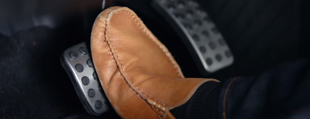 A foot pressing down on the brake pedal of a Mercedes-Benz vehicle