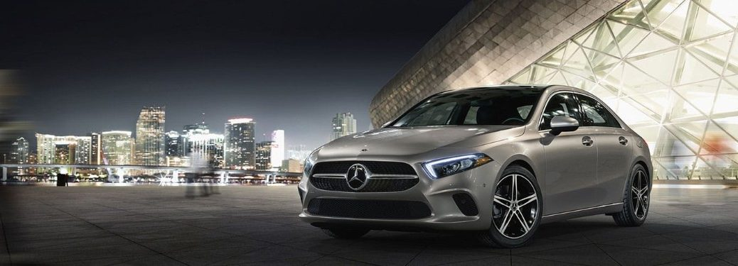 Front driver angle of a silver 2019 Mercedes-Benz A-Class sedan parked with a city in the background