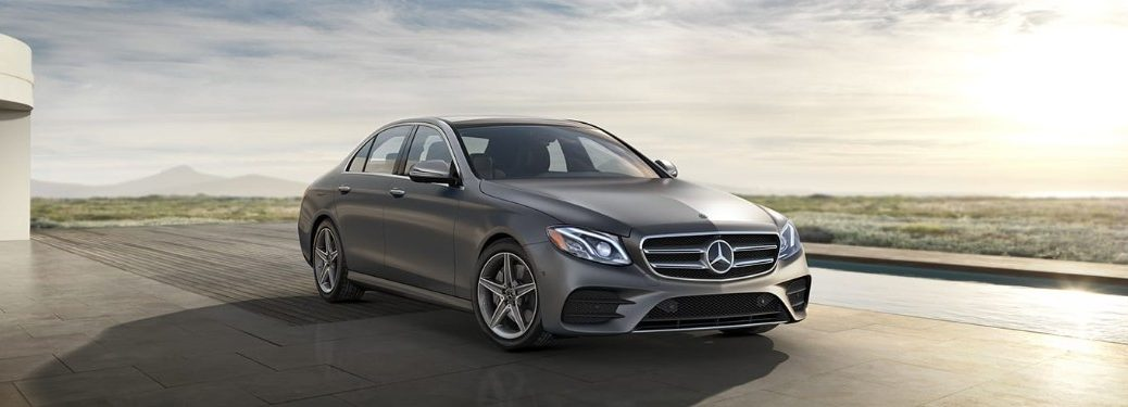 Front passenger angle of a gray 2019 Mercedes-Benz E-Class sedan parked on a roof with the sun shining on it