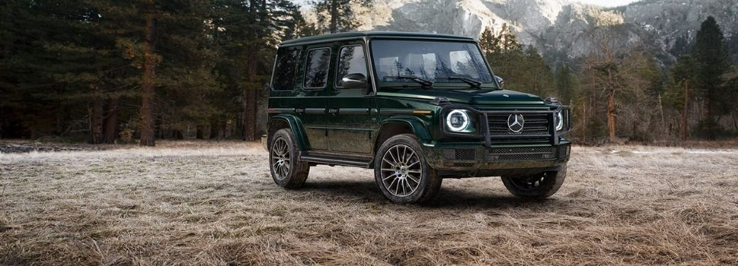 2021 Mercedes-Benz G-Class SUV Front Right-Quarter View parked in a forest with trees and mountains in the background.
