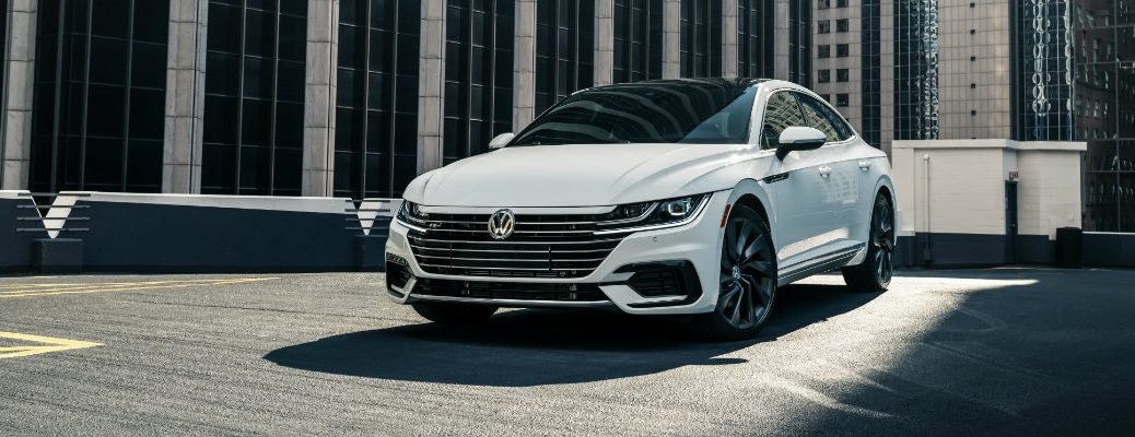 2019 Volkswagen Arteon R-Line exterior shot with white paint color parked on a rooftop and surrounded by skyscrapers