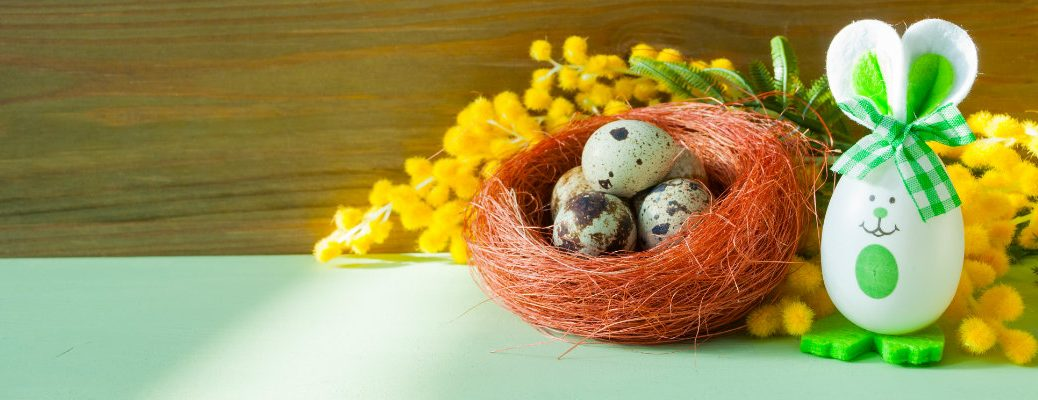 a painted Easter Egg dressed up as a bunny sat next to a nest of green bird eggs and flowers on a table counter