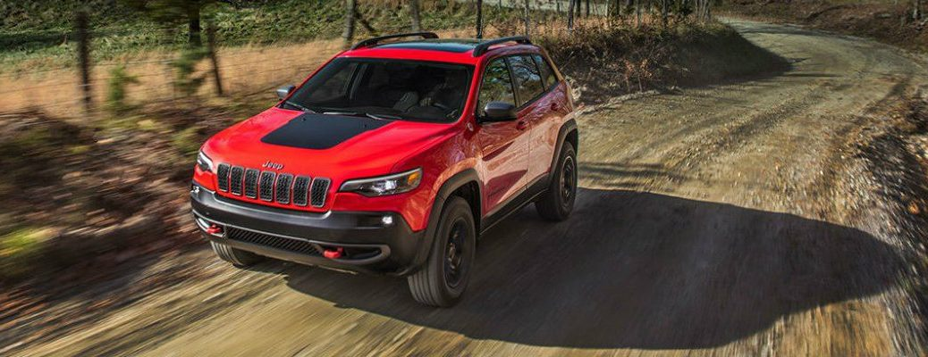 Red Jeep Cherokee driving on country trail