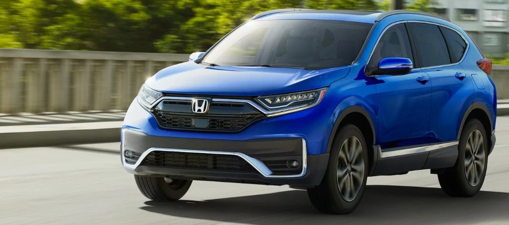 Front driver angle of a blue 2020 Honda CR-V driving down a road