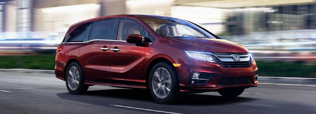 Front passenger angle of a red 2020 Honda Odyssey driving in a city