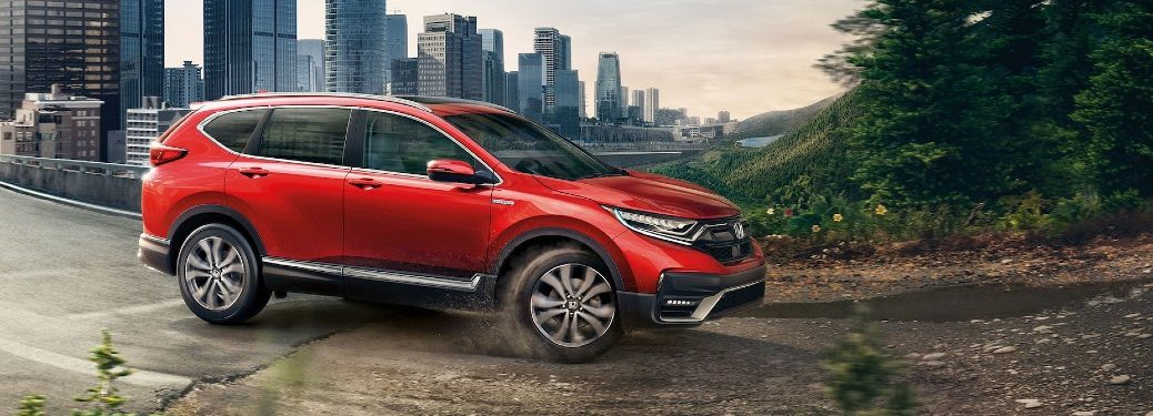 Front passenger angle of a red 2020 Honda CR-V Hybrid driving out of a city onto a trail