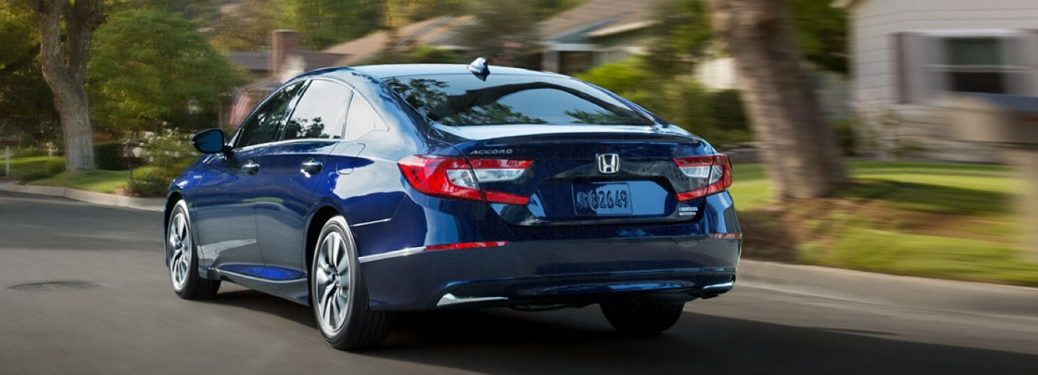 Rear driver angle of a blue 2020 Honda Accord Hybrid driving on a road