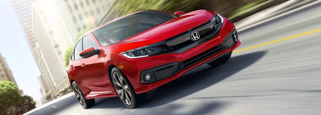 Front passenger angle of a red 2020 Honda Civic sedan driving on a road