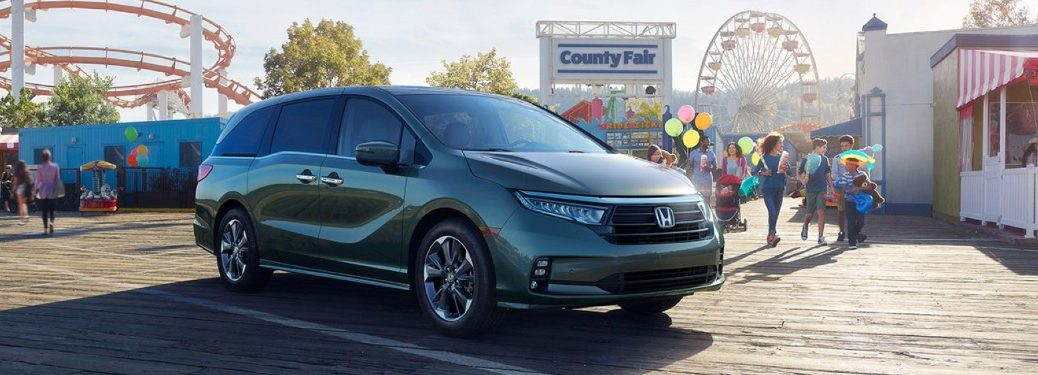 Front passenger angle of a green 2021 Honda Odyssey parked by a fair