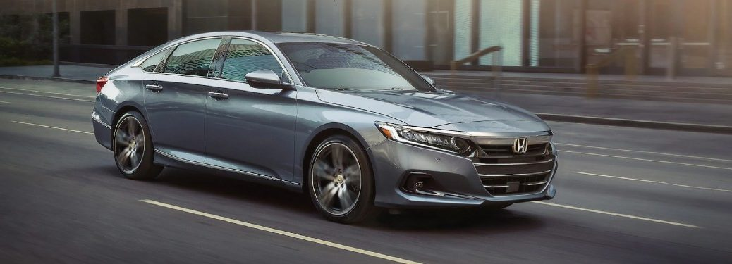 Front passenger angle of a grey 2021 Honda Accord driving on a road