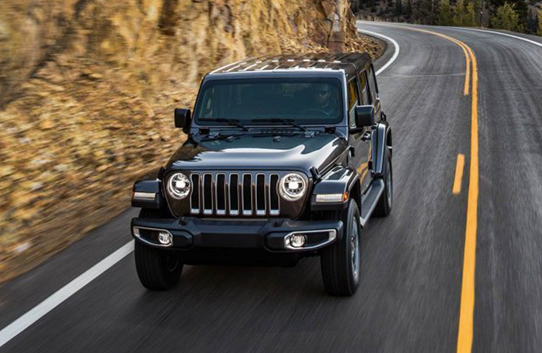 Front view of 2019 Jeep Wrangler driving on rural two-lane road
