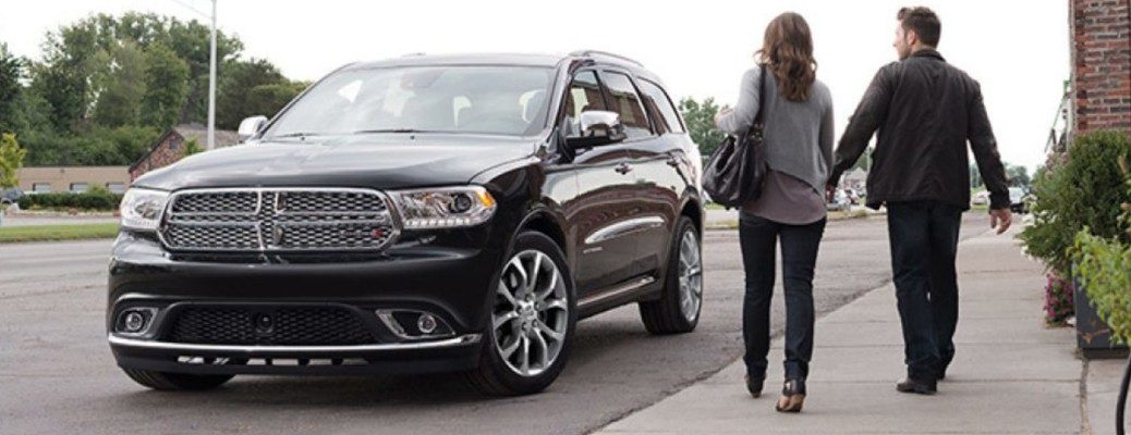 Man and woman walking towards 2019 Dodge Durango parked on city curb