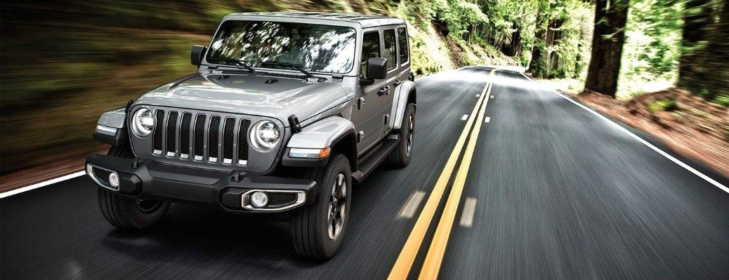 Silver Jeep Wrangler driving on forested road