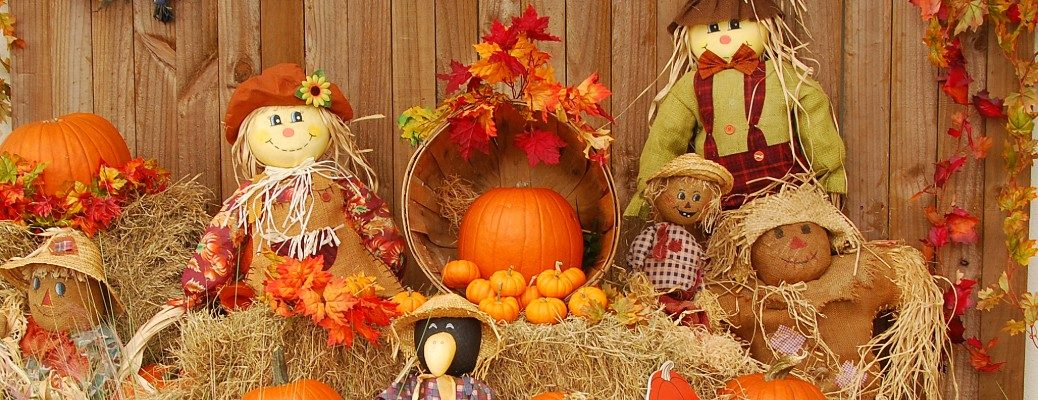 Scarecrows sitting on straw bales with pumpkins