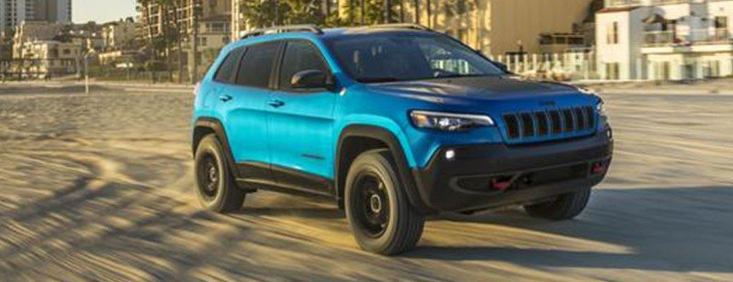 Front view of blue 2020 Jeep Cherokee driving in sand