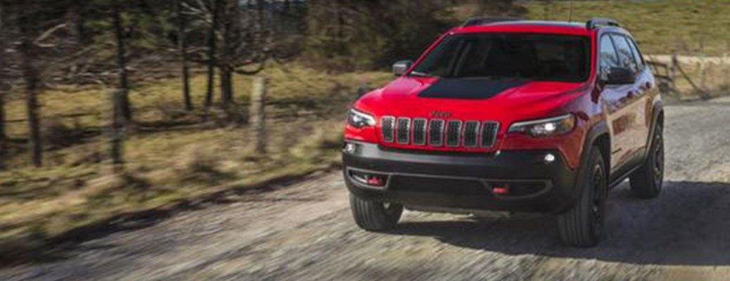 Front view of red 2020 Jeep Cherokee driving on dirt road