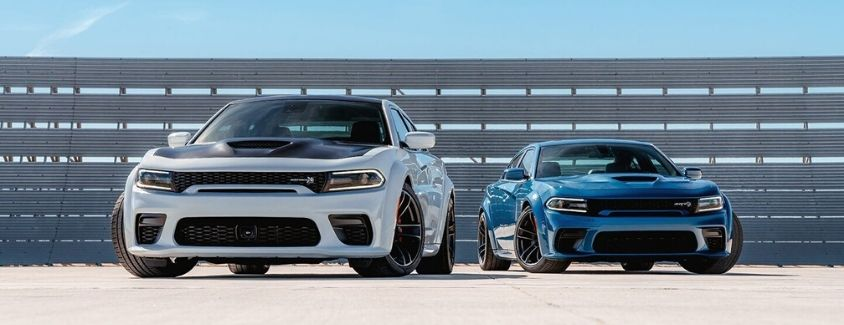 Exterior view of the front of a white 2019 Dodge Charger and a blue 2019 Dodge Charger