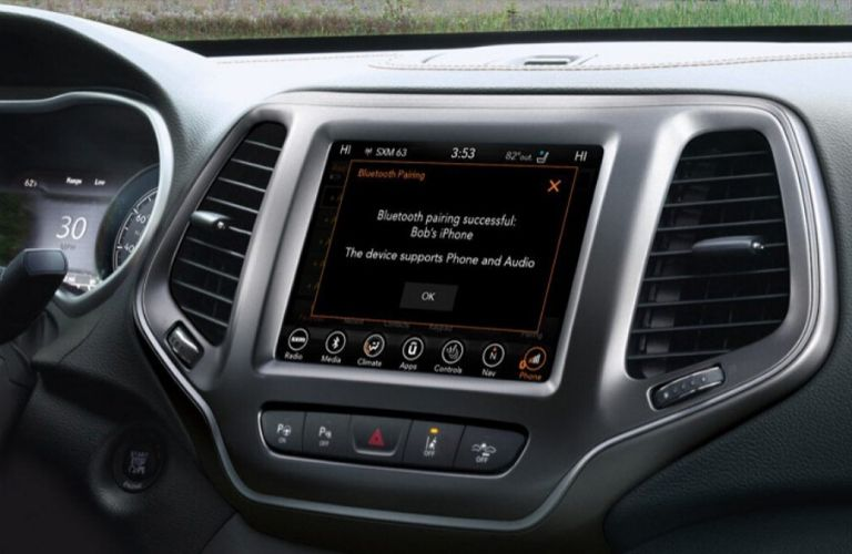 Closeup image of the Uconnect System touchscreen display connecting to Blutooth® inside a Jeep
