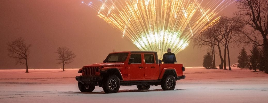 Exterior view of an orange 2020 Jeep Gladiator and fireworks