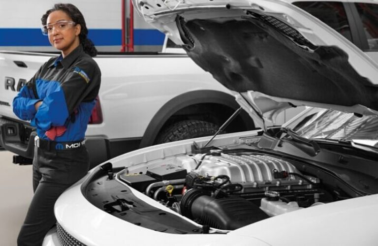 Image of a service technician standing next to a vehicle with its hood propped open