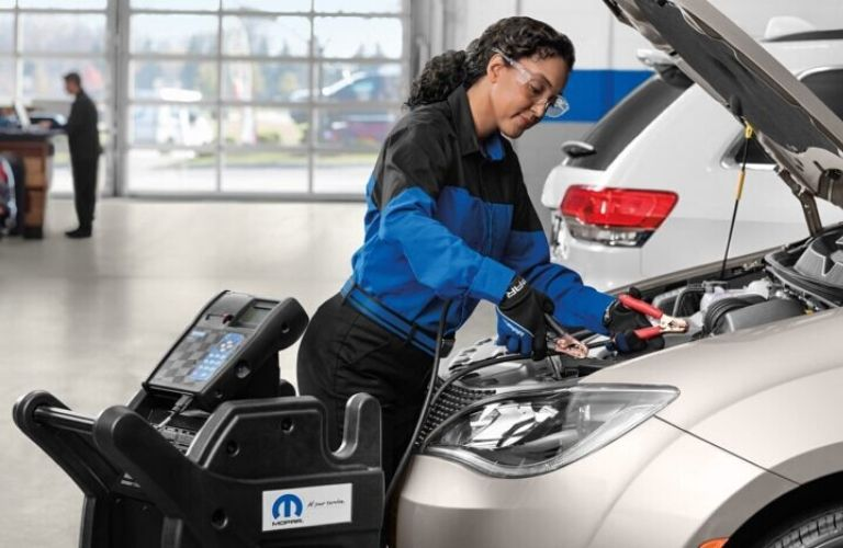 Image of a service technician inspecting a vehicle's battery