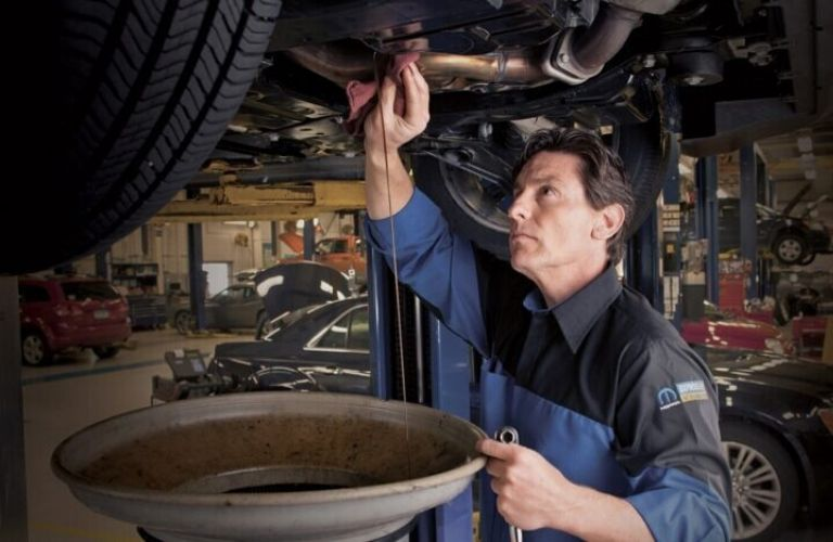 Image of a service technician draining old oil out of a vehicle
