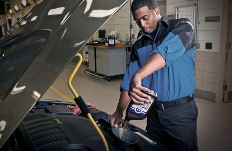 Image of a service technician performing an oil change