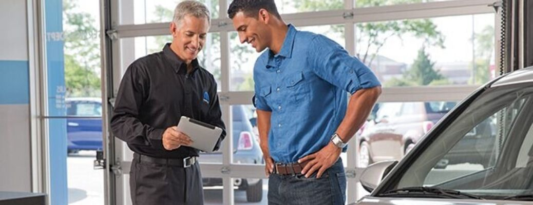 Image of a service technician talking over a multi-point vehicle inspection with a customer