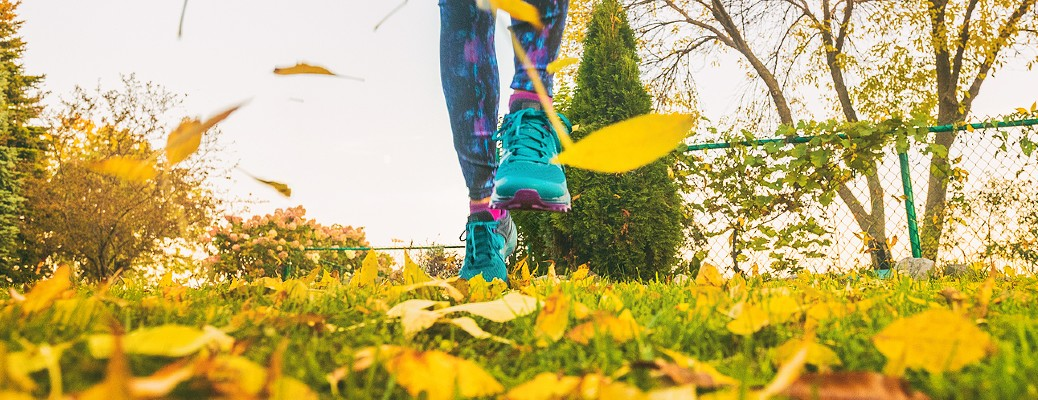 Person in colorful shoes running on leaf-covered grass
