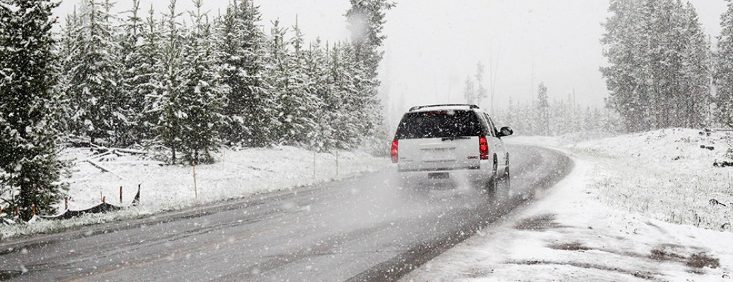 Vehicle driving on snow-covered road in winter