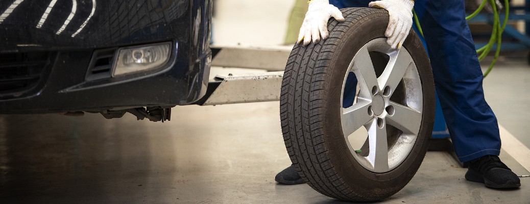 A person with white gloves holding a car tire near a vehicle