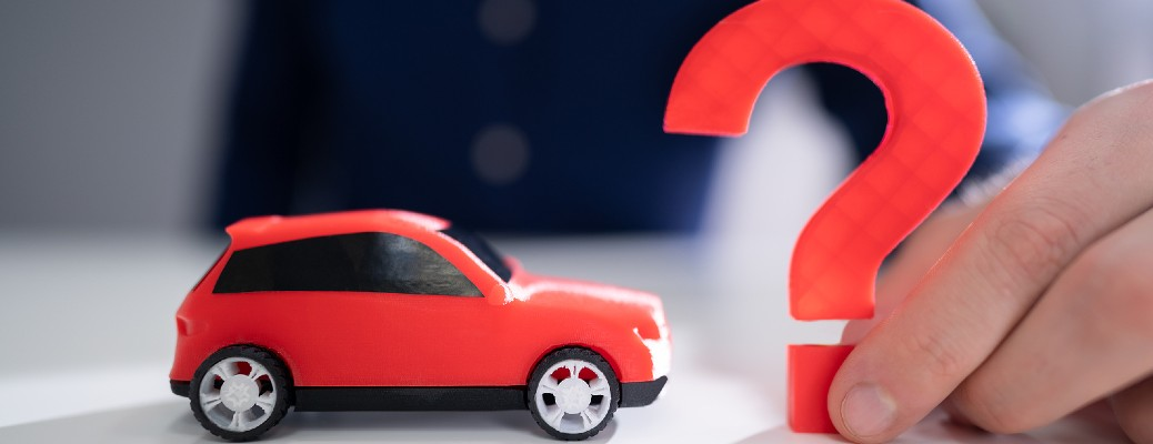 A red toy car next to a slightly larger red-colored question mark, which is held by a human hand