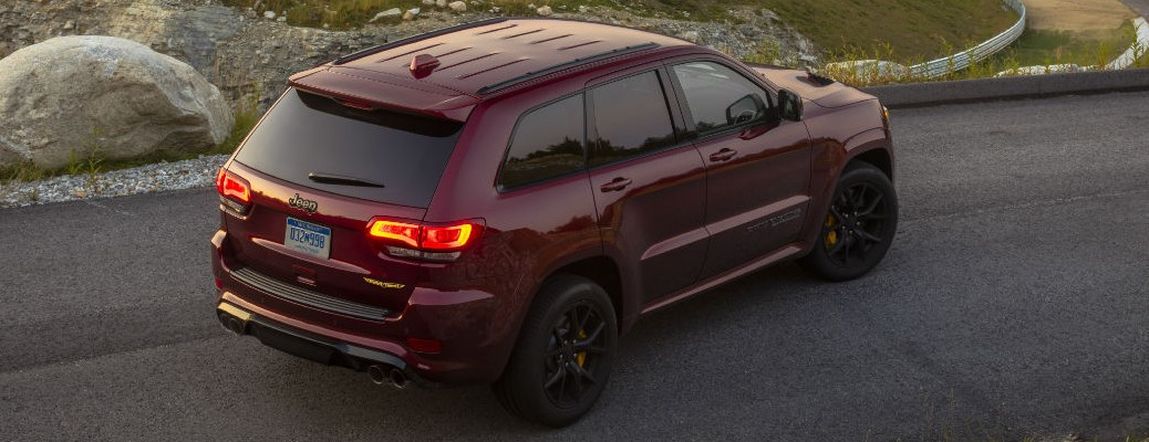 A red-colored 2021 Jeep Grand Cherokee driving on a road.