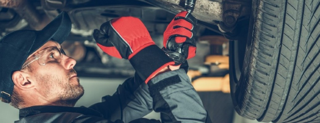 A man in a hat and gloves working on a part under the tire of a car