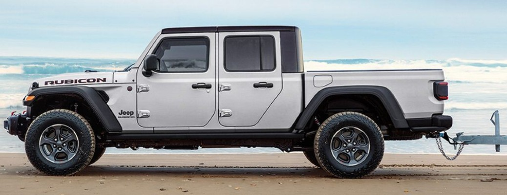 A white-colored 2021 Jeep Gladiator parked on a beach near water