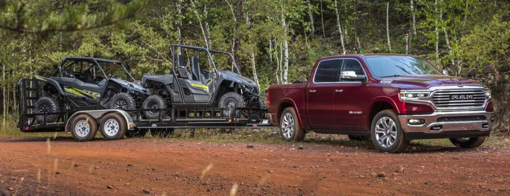 2021 RAM 1500 side view red towing a trailer