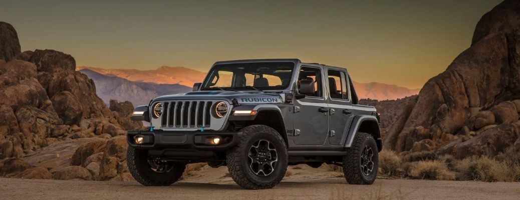 A grey colored Jeep Wrangler 4xe Rubicon parked in the desert overlooking mountains